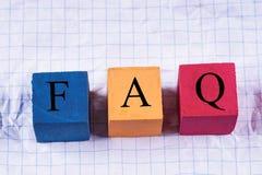 Bunte Würfel mit einem Aufschrift FAQ auf zerknittertem Papier lizenzfreies stockfoto