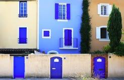 Bunte Wand mit Fenstern und Türen Stockbild