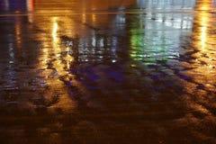Bunte Wasserreflexion auf der Straße Nachtstadtlichter reflektiert in der Pfütze Lizenzfreie Stockbilder