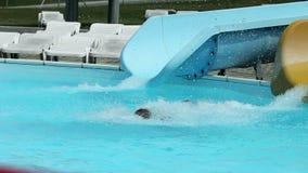 Bunte Wasserrutsche im Pool mit den Leuten, die unten schieben stock footage