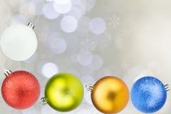 Bunte Weihnachtsbälle mit Schneeflocken auf weißem bokeh Hintergrund Lizenzfreie Stockfotos