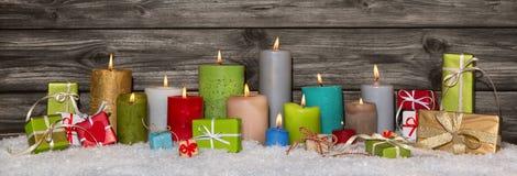 Bunte Weihnachtsdekoration mit Geschenken und brennenden Kerzen Lizenzfreie Stockbilder