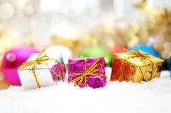Bunte Weihnachtsgeschenke im Schnee Stockfoto