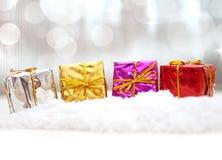 Bunte Weihnachtsgeschenke im Schnee Stockbilder