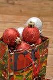 Bunte Weihnachtsgeschenktasche füllte mit Weihnachtsflitter Stockfotografie