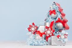 Bunte Weihnachtsinneneinrichtung - metallische Geschenkboxen mit hellen roten und blauen Seidenbändern und Weihnachtsbaum auf wei stockbilder