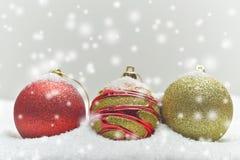 Bunte Weihnachtskugeln auf schneebedecktem Hintergrund Lizenzfreie Stockbilder