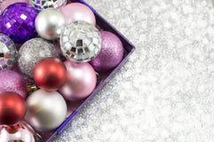 Bunte Weihnachtsverzierungen in einer Schüssel gegen glänzenden Hintergrund Stockfoto