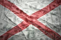 Bunte wellenartig bewegende Alabama-Staatsflagge auf einem amerikanischen Dollargeldhintergrund stockfotos