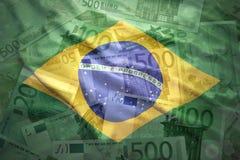 Bunte wellenartig bewegende brasilianische Flagge auf einem Eurohintergrund Stockfotos