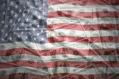 Bunte wellenartig bewegende Flagge Staaten von Amerika auf einem amerikanischen Dollargeldhintergrund Lizenzfreie Stockbilder