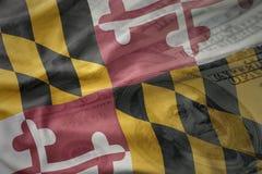 Bunte wellenartig bewegende Flagge von Maryland-Staat auf einem amerikanischen Dollargeldhintergrund Lizenzfreies Stockfoto
