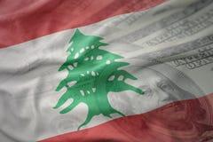 Bunte wellenartig bewegende Staatsflagge vom Libanon auf einem amerikanischen Dollargeldhintergrund Stockbild