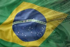 Bunte wellenartig bewegende Staatsflagge von Brasilien auf einem Dollargeldhintergrund Ei auf goldenem Hintergrund Stockbilder