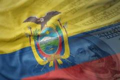 bunte wellenartig bewegende Staatsflagge von Ecuador auf einem Dollargeldhintergrund Ei auf goldenem Hintergrund Stockbild