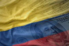 bunte wellenartig bewegende Staatsflagge von Kolumbien auf einem Dollargeldhintergrund Ei auf goldenem Hintergrund Stockfoto