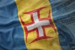 Bunte wellenartig bewegende Staatsflagge von Madeira auf einem amerikanischen Dollargeldhintergrund Stockfotos