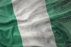 Bunte wellenartig bewegende Staatsflagge von Nigeria auf einem amerikanischen Dollargeldhintergrund Lizenzfreie Stockfotos