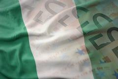 Bunte wellenartig bewegende Staatsflagge von Nigeria auf einem Eurogeld-Banknotenhintergrund Lizenzfreie Stockfotografie