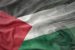 Bunte wellenartig bewegende Staatsflagge von Palästina auf einem amerikanischen Dollargeldhintergrund Stockbilder