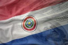 bunte wellenartig bewegende Staatsflagge von Paraguay auf einem Dollargeldhintergrund Ei auf goldenem Hintergrund Stockbild