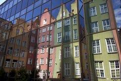 Bunte Wohnungshäuser reflektierten sich in den Fenstern des modernen Gebäudes in Gdansk Lizenzfreie Stockbilder
