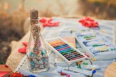 Bunte Zeichenstifte, Acrylfarben und Flasche mit Wünschen Stockfotos