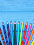 Bunte Zeichenstifte auf blauen Brettern, Schulzubehör, Kopienraum für Text Lizenzfreies Stockfoto