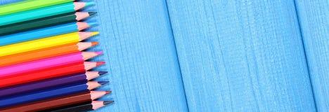 Bunte Zeichenstifte auf blauen Brettern, Schulzubehör, Kopienraum für Text Lizenzfreie Stockfotos