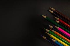 Bunte Zeichenstifte auf einem schwarzen Hintergrund lizenzfreies stockfoto