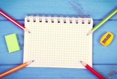 Bunte Zeichenstifte, Bleistiftspitzer, Radiergummi und Notizblock auf Brettern, Schulzubehör, Kopienraum für Text Stockfotos