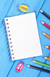 Bunte Zeichenstifte, Bleistiftspitzer und Notizblock auf blauen Brettern, Schulzubehör, Kopienraum für Text Stockbild