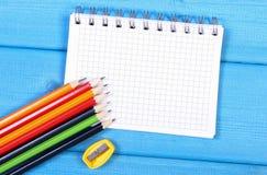 Bunte Zeichenstifte, Bleistiftspitzer und Notizblock auf blauen Brettern, Schulzubehör, Kopienraum für Text Lizenzfreies Stockfoto