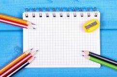 Bunte Zeichenstifte, Bleistiftspitzer und Notizblock auf blauen Brettern, Schulzubehör, Kopienraum für Text Stockfotos