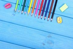 Bunte Zeichenstifte, Bleistiftspitzer und Radiergummi auf blauen Brettern, Schulzubehör, Kopienraum für Text Stockbild