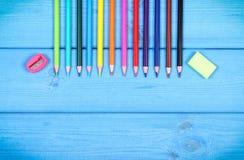 Bunte Zeichenstifte, Bleistiftspitzer und Radiergummi, Schulzubehör, Kopienraum für Text auf Brettern Stockfotografie