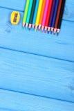 Bunte Zeichenstifte und Bleistiftspitzer auf blauen Brettern, Schulzubehör, Kopienraum für Text Stockfotos
