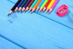 Bunte Zeichenstifte und Bleistiftspitzer auf blauen Brettern, Schulzubehör, Kopienraum für Text Stockfoto