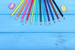 Bunte Zeichenstifte und Bleistiftspitzer auf blauen Brettern, Schulzubehör, Kopienraum für Text Lizenzfreie Stockfotografie