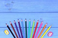 Bunte Zeichenstifte und Bleistiftspitzer auf Brettern, Schulzubehör, Kopienraum für Text Lizenzfreies Stockfoto