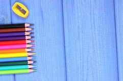 Bunte Zeichenstifte und Bleistiftspitzer auf Brettern, Schulzubehör, Kopienraum für Text Lizenzfreies Stockbild
