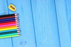 Bunte Zeichenstifte und Bleistiftspitzer, Schulzubehör, Kopienraum für Text auf blauen Brettern Stockbild