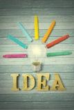 Bunte Zeichenstifte und Glühlampe mit Ideenwort Stockbild