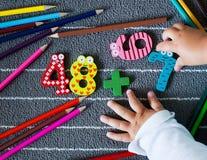 Bunte Zeichenstifte und Zahl mit den kleinen Kleinkindhänden vortraining Stockbild