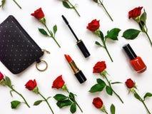 Bunte Zusammensetzung mit roten hellen Rosen und Frauenzubehör Flache Lage auf weißer Tabelle, Draufsicht Stockfotografie