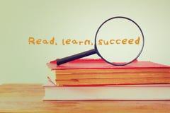 Bunten av böcker och förstoringsglaset med uttrycket lär att läst lyckas books isolerat gammalt för begrepp utbildning Royaltyfri Fotografi