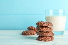 Bunten av chokladkakor med exponeringsglas av mjölkar på den vita tabellen arkivfoto