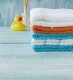 Bunten av färgrika handdukar och badet duckar på tabellen Arkivbild