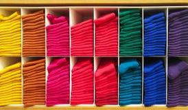 Bunten av färgrika horisontalolika fluffiga badninghanddukar i trähyllan för att shoppa ställer ut Royaltyfri Bild