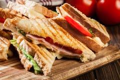 Bunten av panini med skinka, ost och grönsallat skjuter in royaltyfri foto